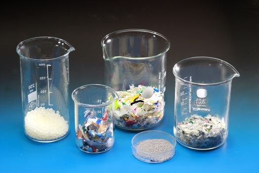 Shredded plastic recyclates in various laboratory glasses